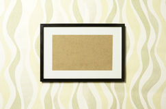 Frame on wallpaper 04. Black wooden frame with white passepartout on modern design wallpaper. In PS any image can be easily put inside the passepartout Royalty Free Stock Photo