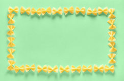 Frame from wheat pasta farfalle on light green background. Random pattern. Flat lay Royalty Free Stock Photography