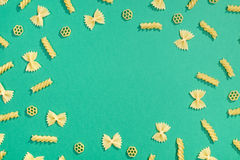 Frame from wheat pasta on green background Stock Photos