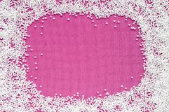 Frame of white beads on a pink fabric with space Royalty Free Stock Image