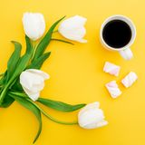 Frame of white tulips flowers with mug of coffee and marshmallows on yellow background. Floral concept. Flat lay, top view. Frame of white tulips flowers with Stock Image