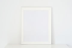 Frame white. On white wooden table, put walls white background Stock Photo
