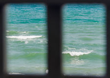 Frame window with view to blue, green sea water waves, seaside w Royalty Free Stock Images