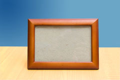 Frame on a wooden table and blue backdrop Stock Photography