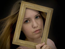 Framed. Woman holding an old picture frame over her face stock photography