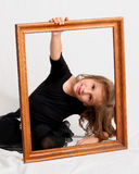Framed. Young girl posing with empty picture frame Stock Photography