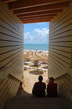 Framed Beach View with teenagers in the shade. Wooden steps lead to the beach Stock Photography