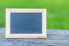 Framed Black Chalkboard on old wood table Stock Photos