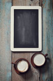 Framed blackboard and coffee. Small wooden framed blackboard with two cups of coffee on wooden background Royalty Free Stock Image