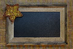 Framed blank textured chalkboard. Script ready. Wooden frame has a twinkling gold and brown star in the corner. Set on mesh background royalty free stock photos