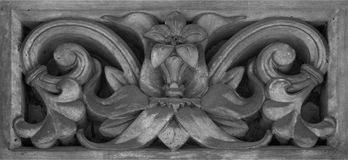 Framed floral detail with single flower. Shot in black and white detail on the sculpture on the facade of this historic building representing some characters / stock photography