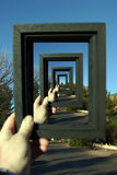 Framed Infinity. My hand holding a black wooden picture frame in Sedona Arizona framing Bell Rock behind a blue sky repeated over and over inside the frame Stock Photo