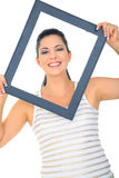 Framed Pretty Young Woman. Beautiful young woman posing through empty frame stock photo