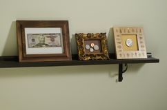 Framed US currency on shelf Stock Photos
