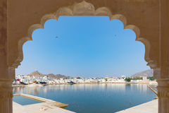 Framed view from archway at Pushkar, Rajasthan, India. Temples, buildings and ghats on the holy water of the lake at sunset. Royalty Free Stock Photography