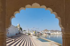 Framed view from archway at Pushkar, Rajasthan, India. Temples, buildings and ghats on the holy water of the lake at sunset. Royalty Free Stock Photos