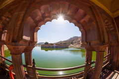 Framed view of the honey toned impressive Amber Fort, famous tourist attraction at Jaipur, Rajasthan, India. Daylight, clear blue. Framed view of the honey toned stock images