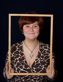 Framed young woman. Portrait of young woman with a frame against a blue background Royalty Free Stock Images
