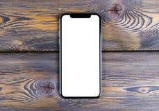 Frameless modellsmartphone med den tomma skärmen och den moderna ramen mindre design på kontorsskrivbordet Isolerad vit skärm kop royaltyfri bild