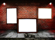 Frames. Three frames along a brick wall with concret flooring. Concept for art show Stock Photos