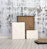 Frames and Boards Inside Empty Room. Frames and Boards Emphasizing Copy Space, Leaning on Unfinished Concrete Wall Inside an Empty Room with White Flooring Royalty Free Stock Images