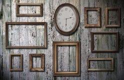 Frames e relógio vazios na parede de madeira Fotos de Stock