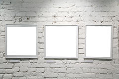 Frames on the wall. Three frames on the white brick wall Stock Photos