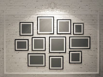 Frames on white brick wall. With spotlights Royalty Free Stock Photos