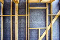 Framework of the house wall, of boards and timber, a window, a vapor barrier from the inside. Framework of the house wall, of boards and timber, a window, a grey royalty free stock photos