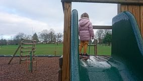 Girl in pink coat standing on a climbing frame royalty free stock photos