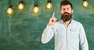 framför den begreppsmässiga bilden för begreppet 3d lösningen Skäggig hipster i skjortan, svart tavla på bakgrund Mannen med skäg Royaltyfri Bild