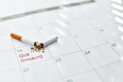 framförd anti bild som 3d avslutas rökning Slut upp av den brutna cigaretten som ligger på kalender Arkivbild