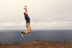 Framgång- eller segerbegrepp - glad manbanhoppning arkivfoto