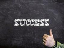 Framgång som är skriftlig på en svart tavla med tummar, Up tecknet royaltyfri bild