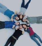 Framgångbegrepp - lyckligt studentlag som ligger i en cirkel och en holdi Royaltyfri Bild