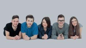 Framgångbegrepp - lyckligt studentlag som ligger på en vit affischloo Arkivfoton