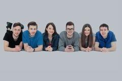 Framgångbegrepp - lyckligt studentlag som ligger på en vit affischloo Arkivbild