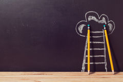 Framgångbegrepp med blyertspennor och stegen över den svart tavlan Fotografering för Bildbyråer