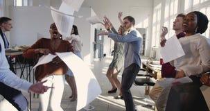 Framgångberömparti på det moderna multietniska kontoret Lycklig grupp för affärsfolk som gör rolig dans på den moderiktiga arbets arkivfilmer