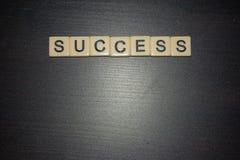 Framgångbokstavstegelplattor uppställda på en svart bakgrund Arbeta tillsammans, finna framgång i liv, affären, utbildning öppet  fotografering för bildbyråer