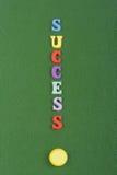 FRAMGÅNGord på grön bakgrund som komponeras från träbokstäver för färgrikt abc-alfabetkvarter, kopieringsutrymme för annonstext royaltyfri foto
