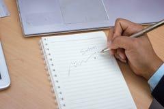 Framgångbegreppet skriver ner i ett papper Arkivbild