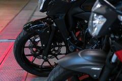 Framhjul av den moderna svarta motorcykeln på betong- och metallgro arkivfoton