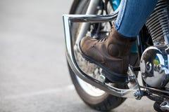 Framhjul och kvinnligt ben med den skyddande kängan på ställningar av avbrytarmopeden, copyspace Royaltyfria Bilder