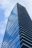 Frami esteriore degli alberi del cielo blu di riflessione di vetro nuvoloso del grattacielo immagine stock