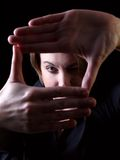 Framing. Woman framing her face with hands - low key effect Royalty Free Stock Image