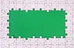 Framing in the form of a rectangle, made of a white jigsaw puzzle around the green space. Framing in the form of a rectangle, made of a white jigsaw puzzle Stock Photography