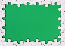 Framing in the form of a rectangle, made of a white jigsaw puzzle around the green space.  Royalty Free Stock Image