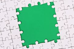 Framing in the form of a rectangle, made of a white jigsaw puzzle around the green space.  Royalty Free Stock Photos