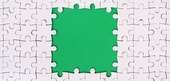 Framing in the form of a rectangle, made of a white jigsaw puzzle around the green space. Framing in the form of a rectangle, made of a white jigsaw puzzle Royalty Free Stock Image